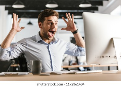 Shocked screaming business man using computer and rejoices while sitting by the table in office