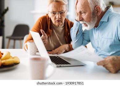 Shocked senior couple reading their home finances on laptop
