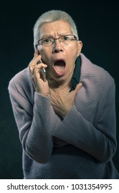 Shocked senior lady can't believe the news she's receiving over her cell phone