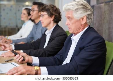Shocked senior man using smartphone at meeting