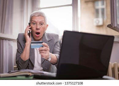 Shocked senior woman can't believe her credit card balance, arguing with the bank clerk