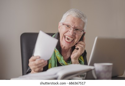 Shocked senior woman raging on her cell phone over her pricey electricity bills