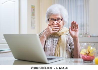 Shocked senior woman using laptop at home.