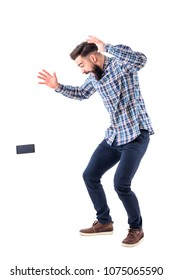 Shocked sloppy clumsy bearded man dropping mobile phone falling on the ground in mid air. Full body isolated on white background.