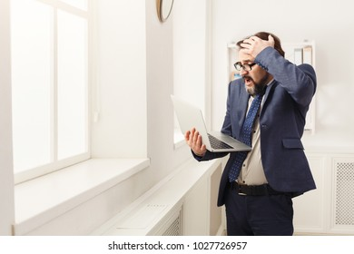 Shocked stressed businessman looking at laptop screen, touching his forehead, standing at window in modern office. Job problems concept, copy space