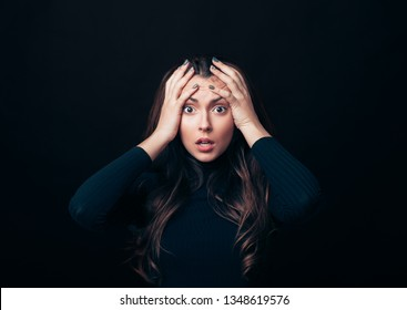 Shocked stressed woman touching head in panic attack looking in camera isolated on black background
