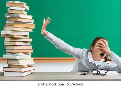 Shocked student closes her eyes to a lot of books. Portrait of young girl with shocked facial expression in school. Back to school!