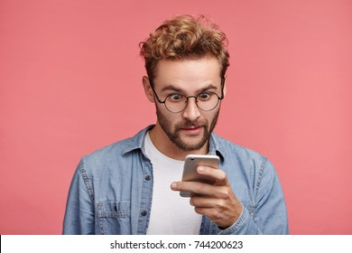 Shocked stylish hipster guy reads news online, uses free internet connection on modern cell phone, finds out about car accident in neigbour strict. Astonished male model recieves strange message