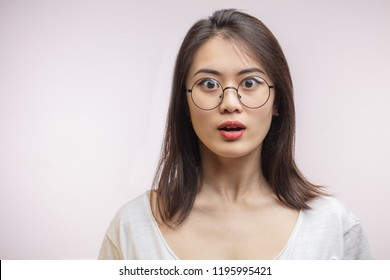 Shocked surprised Asian woman in optical glasses looking at camera. Disbeief and surprisment, omg concept. Korean female with bugged eyes expresses fear or astonishment