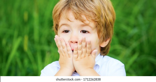 Shocked and surprised boy. Funny child boy. Smiling amazed or surprised child boy. Child expressing surprise with his hands in his face.