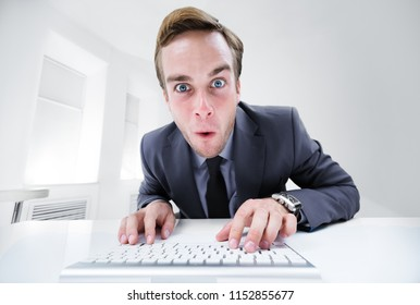Shocked or surprised businessman in black suit, working with computer at office. Success in business, job and education concept.