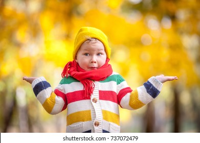 Shocked and surprised child. Cheerful little boy opens his mouth in surprise. child walking in autumn park with red scarf on neck.