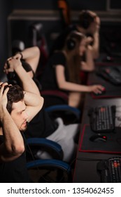 Shocked surprised ESport Gamers playing in competitive game in gaming club put their head in his hands in overwhelming joy realising that they have won the game.