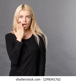 Shocked and surprised girl screaming covering mouth her hands