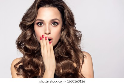 Shocked and surprised girl screaming covering  mouth her hands.Curly hair woman amazed.Beautiful girl  with curly hairstyle and red nails manicure.Presenting your product.Expressive facial expressions