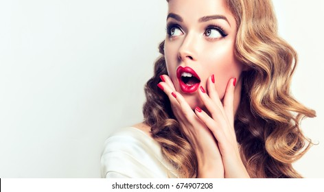 Shocked and surprised girl screaming and  looking to the side presenting  your product . Curly hair woman amazed .Beautiful girl  with curly hair and red nails manicure. Expressive facial expressions