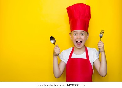 Shocked and surprised girl screaming in a red chef's suit holding a spoon and fork on yellow background with copy space