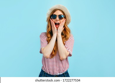 Shocked surprised girl in sunglasses. glasses and a summer hat, the girl covers her mouth with her hands on an isolated blue background