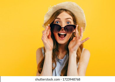 Shocked surprised girl in sunglasses and a summer hat, on a yellow background. Travel, vacation, summer