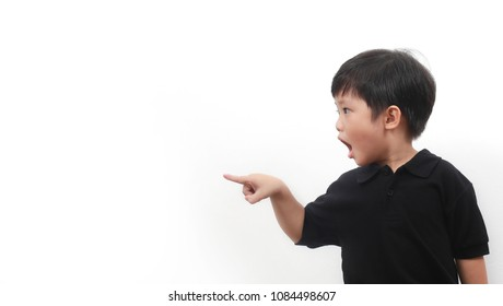 Shocked and surprised little Asian boy open his mouth with hand and finger pointing to side, isolated on white background.