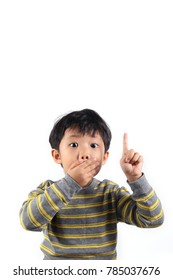 Shocked and surprised little Asian boy covered his mouth with hand and finger pointing up, isolated on white background.