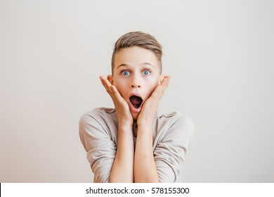 Shocked or surprised  little boy keeping mouth open and touching face with hands