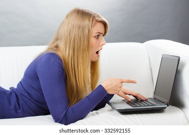 Shocked, surprised and worry woman lying on sofa, using and showing laptop, typing on computer keyboard, surfing internet, modern technology