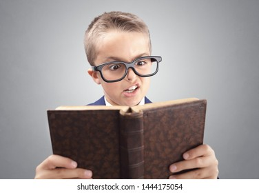 Shocked and surprised young executive businessman boy reading a book concept for confusion, disbelief, surprise and shock