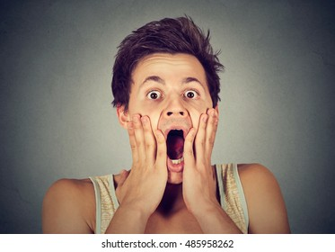 shocked surprised young man in full disbelief with hands on face screaming