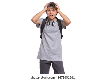Shocked teen boy in cap with headphones and backpack, isolated on white background. Surprised child puts his hands to head and looking at camera. Emotional portrait of teenager guy Back to school.