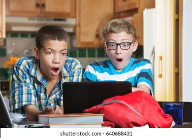 Shocked teen males looking at laptop computer at home