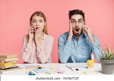 Shocked terrified female and male students recieve call on mobile phones, remember about exam too late, look with jaw dropped, isolated over pink background. Surprised team of workers forget something