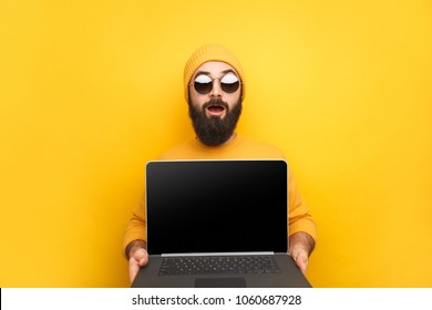 Shocked trendy hipster in sunglasses and yellow hat showing new modern laptop device.