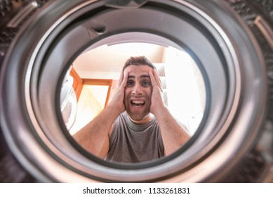 Shocked upset Young man Looking At Stained Bleached Cloth In Washing Machine. View from the inside of washing machine.