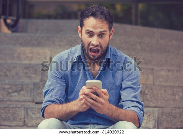Shocked upset young man looking at his mobile phone seeing bad news or reading text message sitting on stairs outside corporate building. Human emotion, reaction, expression