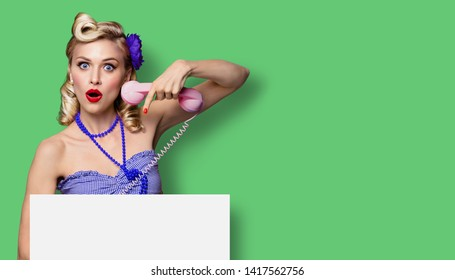 Shocked or very happy woman with phone and blank signboard. Pin up girl, keeping mouth open - unbelievable sales concept. Retro fashion and vintage. Green color background. Copy space for some text.