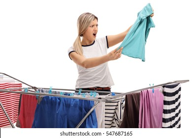 Shocked woman behind a clothing rack dryer looking at a shirt isolated on white background