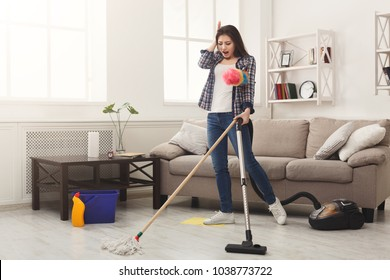Shocked woman cleaning house with lots of tools. Young tired girl washing floor with mop and vacuum cleaner, copy space