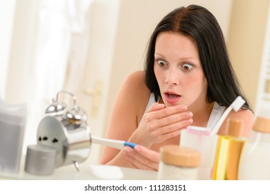 Shocked woman holding positive pregnancy test in the bathroom