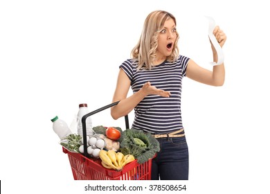 Shocked woman holding a shopping basket full of groceries and looking at the bill in disbelief isolated on white background