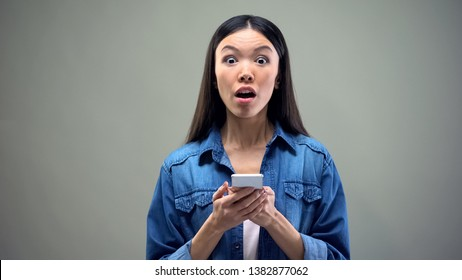 Shocked woman holding smartphone, impressed by discounts in brand clothes shops