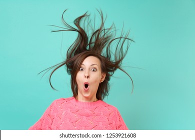 Shocked woman in knitted sweater with fluttering hair keeping mouth wide open, looking surprised isolated on blue background. Sincere emotions lifestyle concept. Mock up copy space, living coral color