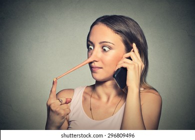 Shocked woman with long nose talking on mobile phone isolated on grey wall background. Liar concept. Human face expressions, emotions, feelings.