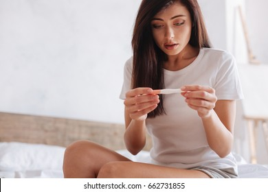 Shocked woman looking at control line on pregnancy test