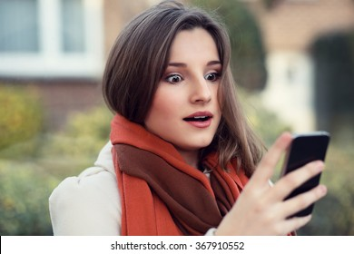 Shocked woman looking at mobile phone. Closeup portrait headshot beautiful young girl surprised student reading sms isolated cityscape outdoor background. Multicultural mixt race asian russian model