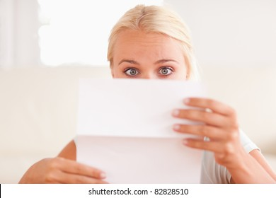 Shocked woman reading a letter in her living room