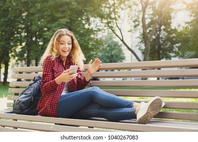 Shocked woman reading news on the smartphone on the bench outdoors. Technology, social media, education and freelance concept, copy space