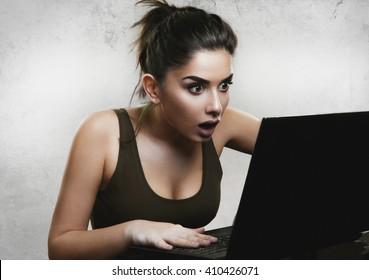 Shocked woman reading news on laptop
