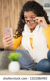 shocked woman sees embarrasing picture in screen of smart phone