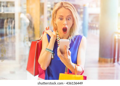 Shocked woman at the shopping mall looking at the phone